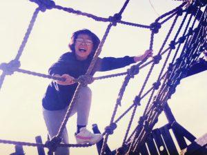 小学校時代の写真。公園のアスレチックでネットを楽しそうな顔で登っているところ。
