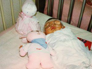 1989年夏、白内障の手術で入院しているときの写真。ピンク色のくまの人形とともにベッドに寝かされている。